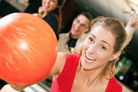 kugel: Group of four friends in a bowling alley having fun, three of them cheering the one in charge to throw the ball