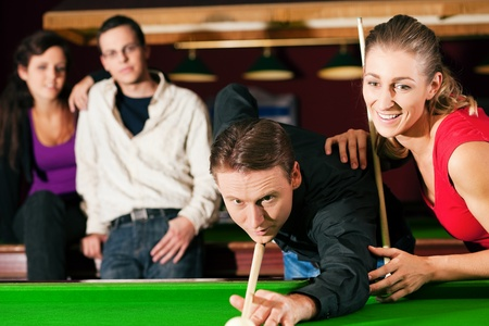 pool table: Group of four friends in a billiard hall playing snooker Stock Photo