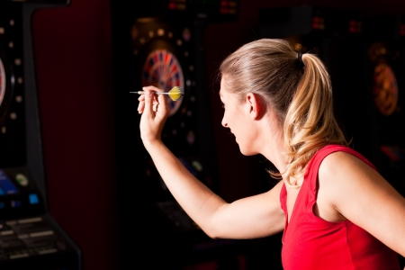 Woman playing darts aiming with the dart to hit the target Stock Photo - 12902745