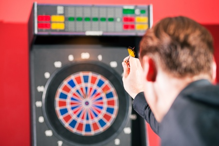 Man playing darts aiming with the dart to hit the target