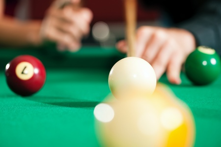Couple  only hands to be seen   in a billiard hall playing pool, close-up shot on the balls photo