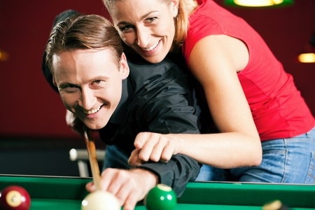 pool table: Couple  man and woman  in a billiard hall playing snooker