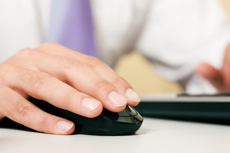 Man  only hand to be seen  using a wireless mouse to operate a computer