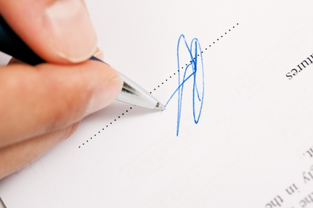 Man  only hand to be seen  signing a contract or another document  fake signature, focus on pen  photo