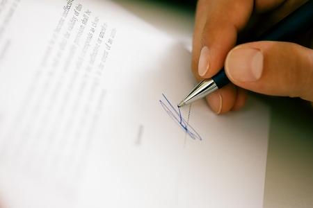 firmando: El hombre s�lo puede ver la mano de la firma de un contrato u otra firma de documento falso