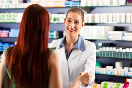 women s health: Female pharmacist consulting a female customer in her pharmacy