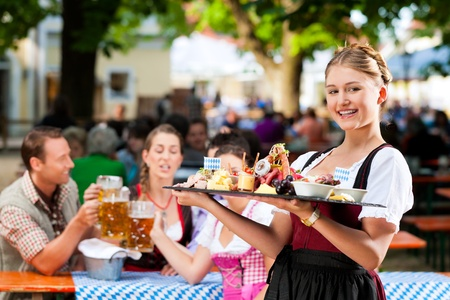 octoberfest: Beer garden restaurant in Bavaria, Germany - beer and snacks are served, the waitress also wears traditional costume