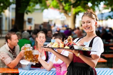 octoberfest: Restaurante bar al aire libre en Baviera, Alemania - la cerveza y los aperitivos se sirven, la camarera tambi�n lleva traje tradicional