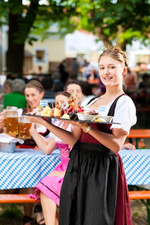 eating in the garden: Beer garden restaurant in Bavaria, Germany - beer and snacks are served, the waitress also wears traditional costume