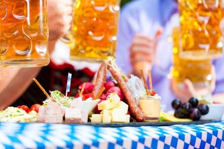 hombre comiendo: Restaurante bar al aire libre en Baviera, Alemania - la cerveza y los aperitivos se sirven, se centran en la comida