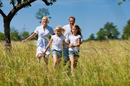 Happy Family with two girls running in a meadow in summer photo