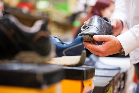 Customer holding formal shoe at supermarket Stock Photo - 13185043