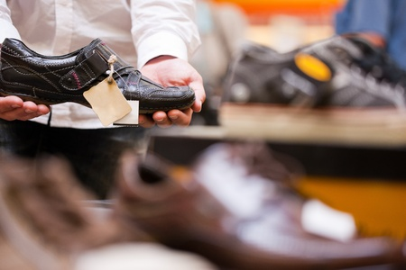 Customer holding stylish shoe at footwear department in supermarket photo