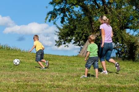 women playing soccer: Happy family is playing soccer in summer in a beautiful landscape Stock Photo