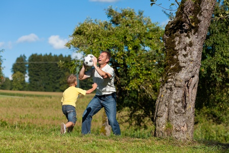 Happy family is playing soccer in summer in a beautiful landscape photo