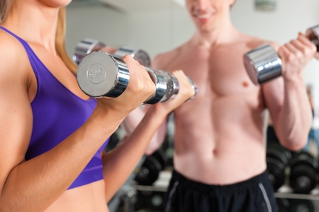 strengthen: Young couple - man and woman - is exercising with barbell in gym to strengthen the muscles