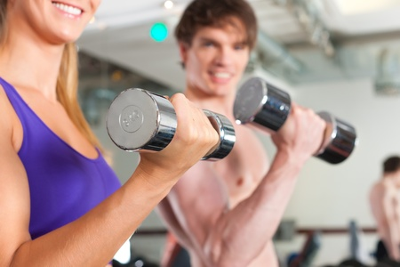 Young couple - man and woman - is exercising with barbell in gym to strengthen the muscles photo