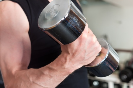 Young man is exercising with barbell in gym to strengthen the muscles, close-up photo