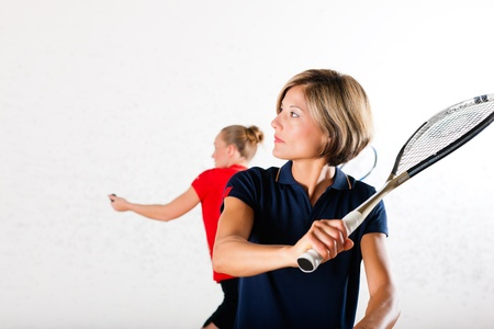 Endurance: Two women playing squash as racket sport in gym, it might be a competition