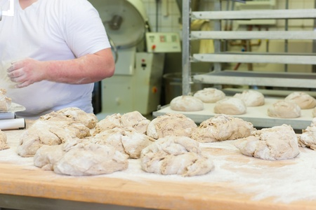 Male baker baking fresh bread in the bakery photo