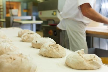Man bakker bakken vers brood in de bakkerij