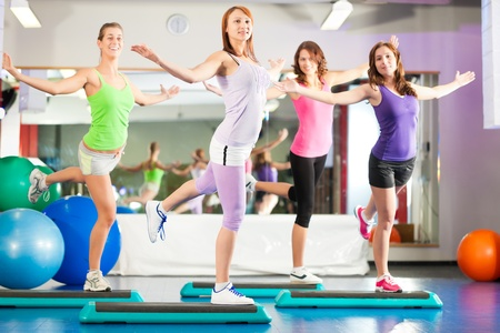 fat burning: Fitness - Young women doing sports training or workout with stepper in a gym