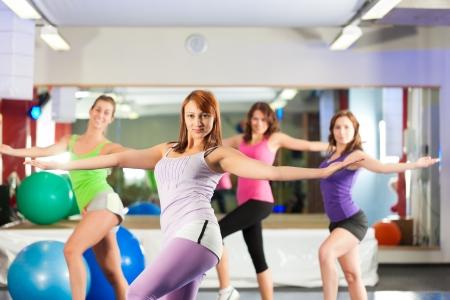 fitness danse: Fitness - Les jeunes femmes font la formation sportive ou d'entra�nement avec moteur pas � pas dans un gymnase