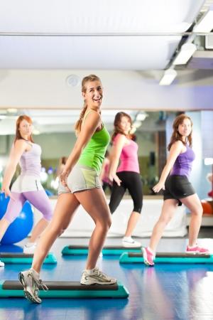dynamic movement: Gimnasio - Las mujeres j�venes haciendo el entrenamiento de deportes o ejercicios con paso a paso en un gimnasio