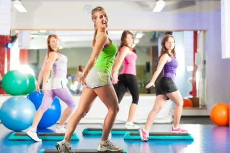 group fitness: Fitness - Young women doing sports training or workout with stepper in a gym