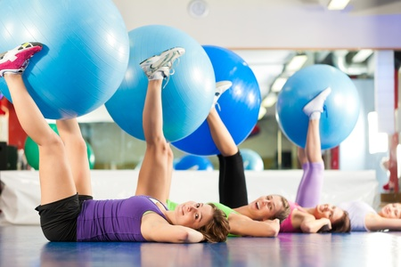 Fitness - Young women doing sports training or workout with gymnastic ball in a gym Stock Photo - 13190187