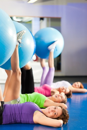 Fitness - Young women doing sports training or workout with gymnastic ball in a gym photo