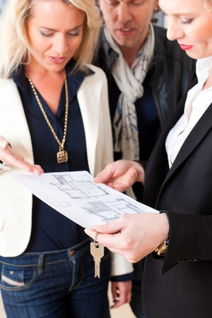 Young realtor explain lease agreement or purchase contract with floor layout to couple in an apartment, close-up Stock Photo - 13190197