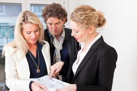 Young realtor explain lease agreement or purchase contract with floor layout to couple in an apartment, close-up photo
