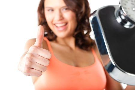Diet and weight - young woman with a scale, she is happy about the success Stock Photo - 13503254