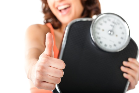 Diet and weight - young woman with a scale, she is happy about the success photo