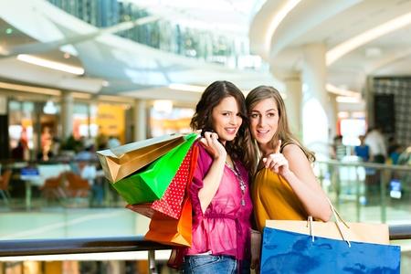 centro comercial: Dos amigas con bolsas de compras que se divierten mientras hacen sus compras en un centro comercial