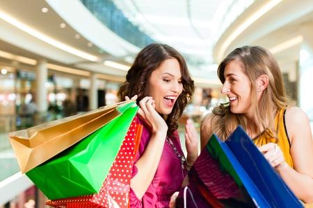 chicas comprando: Dos amigas con bolsas de compras que se divierten mientras hacen sus compras en un centro comercial