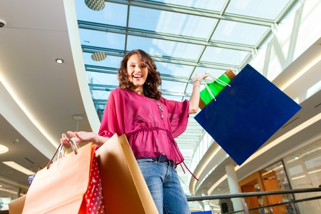 Young happy woman with shopping bags having fun while shopping in a mall Stock Photo - 13190904
