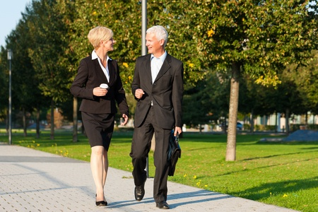 Business people - mature or senior - talking outdoors and walking in a park photo