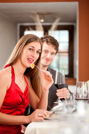 dinner date: Portrait of a happy woman eating food with man sitting behind having drink Stock Photo