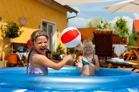 bikini pool: Children - they are sisters - playing in water with a ball in the garden in front of the house