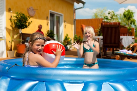 enfant maillot: Les enfants - ils sont s?urs - � jouer dans l'eau avec une balle dans le jardin en face de la maison