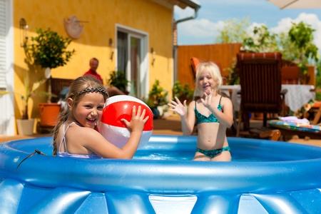 splash pool: Los ni�os - que son hermanas - jugando en el agua con una pelota en el jard�n en frente de la casa