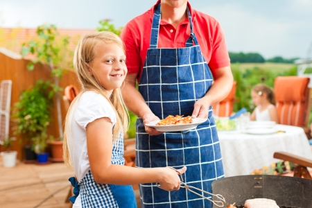 apron: Happy family having a barbecue in summer; the father and a child standing at the grill
