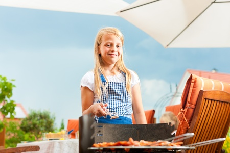 Happy family having a barbecue in summer; the daughter is standing at the grill photo