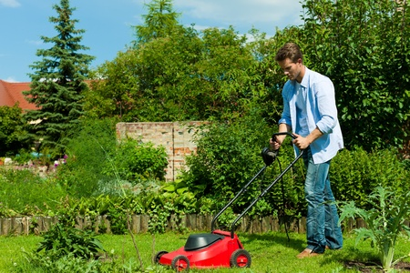 red grass: Young man is mowing the lawn in summer with a mowing machine Stock Photo