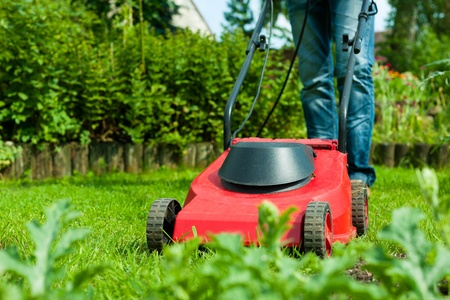 Young man - only legs to be seen - is mowing the lawn in summer with a mowing machine Stock Photo
