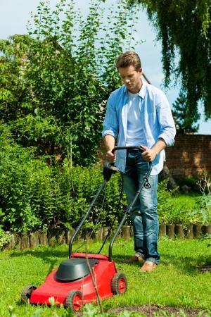 jardinero: El hombre joven está cortando el césped en el verano con una máquina de cortar el césped