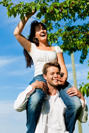 Happy couple eating cherries in summer in a garden, he is carrying her on his shoulders photo
