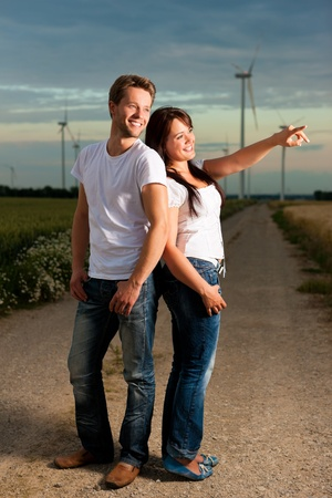 outdoor electricity: Young and powerful couple in front of energy windmill in the evening, a storm is coming